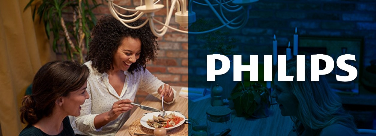 Philips logo with three women eating at table under chandelier